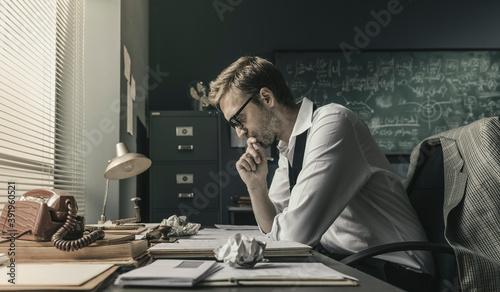Stampa su Tela Brilliant mathematician sitting at desk and studying math formulas