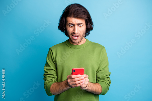 Fototapeta Photo of furious man staring phone bad news problem trouble wear sweater isolated on blue color background obraz