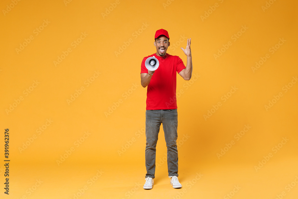 Fototapeta Full length fun crazy delivery employee african man in red cap blank t-shirt uniform work courier service concept hold scream in megaphone announces sale Hurry up isolated on yellow background studio.