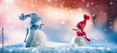 Little knitted snowmen on soft snow on blue background Fototapete
