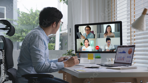 Business man talking about sale report in video conference.Asian team using laptop and tablet online meeting in video call.Working from home, Working remotely and Self isolation at home