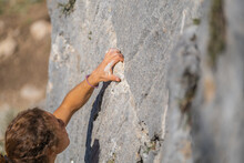 Close-up Of A Young Woman's Hand Holding Onto The Stone While Climbing