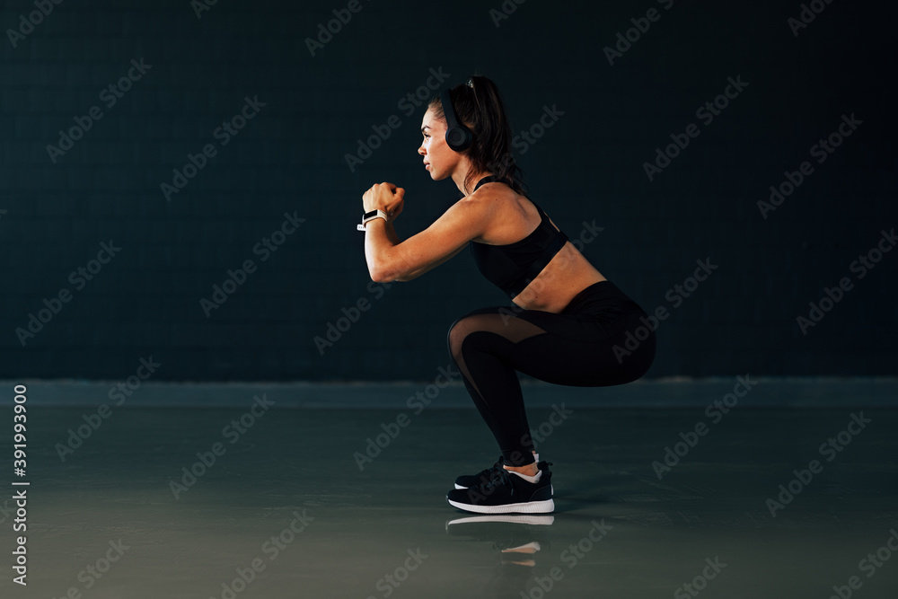 Fototapeta Side view of muscular woman with headphones doing squats in gym