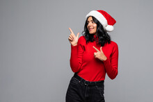 Beautiful Smiling Christmas Santa Woman Pointing Up Showing Copyspace. Isolated On Gray Background.