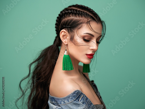 Brunette girl with perfect makeup. Beautiful model woman with curly hairstyle. Care and beauty hair products. Lady with braided hair. Model with jewelry. Turquoise background