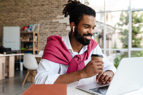 Smiling african american guy drinking coffee while working with laptop - fototapety na wymiar