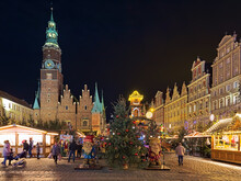 Wroclaw, Poland. Christmas Market On Market Square Close To Old Town Hall In Night. Figures Of Two Dwarfs, Which Are Symbols Of The City Of Wroclaw, Are Located In The Foreground.