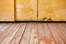 A Fragment Of A Living Room With An Old Wooden Floor With Peeling Paint And A Dilapidated Wardrobe. The Concept Of Poverty And Devastation