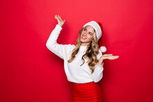 Beautiful Young Woman Wearing Santa's Hat Looking Up With Arms Open, Isolated On Red Background