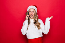 Happy Cute Woman In Santa Hat Talking On Cell Phone Over Red Background
