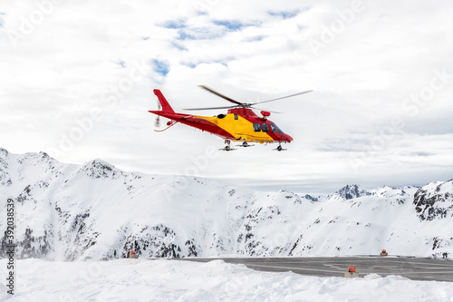 Mountain ski life rescue medic helicopter taking-off from station helipad to search injured skiers and help at accident Fotobehang