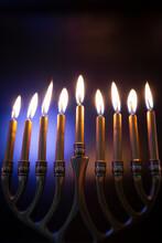 Hanukah Candles Lit In Menorah Against Colorful Background