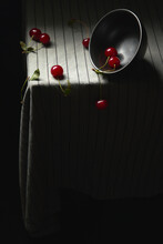 Juicy Red Cherries And An Inverted Bowl On A Striped Tablecloth.