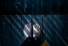 Looking Down On Bare Feet Standing On Wood Deck With Lines Of Light