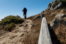 Hiker Walking Up Hill On Coastal Trail In California With Blue Sky