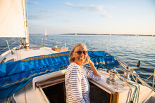 Middle Age Woman Enjoying Summer Sail During Golden Hour