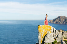 Woman Standing On The Edge Of A Rocky Cliff In The Cíes Islands, Galicia