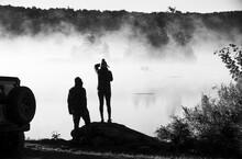 Couple Witnesses Sunrise On Steam Fog Enveloped Vermont Lake Scene.