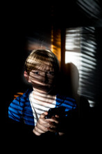 Tween Holding Cell Phone Looking At Camera Indoors In Mottled Light