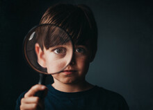 Portrait Of Young Boy Holding A Magnifying Glass Over One Eye.