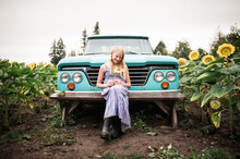 Young Girl Holding Sunflower B...