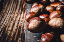 Close-up Of Several Chestnuts In A Glass Dish, On A Wooden Table. Hori