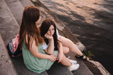 Girlfriends Embracing While Sitting On Steps By River In City