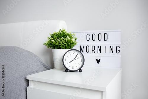 Fotografija good morning concept - close up of alarm clock, houseplant and lightbox with go