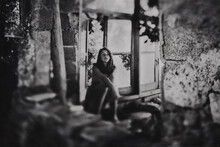 Girl Sitting In Old Derelict H...