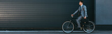 Young Businessman Holding Briefcase While Riding Bicycle Outdoors, Banner