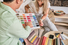 Fabric Salesman Shows A Lady The Color Chart