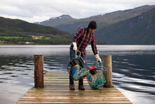 A Fisherman Collecting His Crab Pots On A Fjord In Norway
