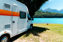 RV Motorhome In Front Of A Blue Lake With Mountains And A Red Kayak