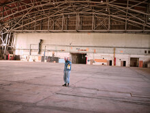 A Man Dressed In Denim Holds A Can Of Paint In A Large Airplane Hanger