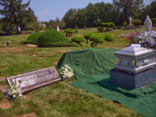 A Casket With Flowers Sits Beside A Gravesite Ready For Burial.
