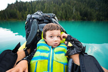 Boy Wearing PFD Rests Against Backpack On Inflatable Boat On Blue Lake