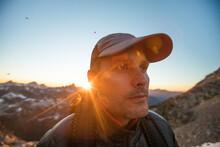Portrait Of Backpacker Wearing Hat On Mountain Ridge.