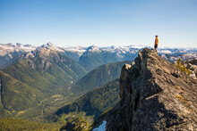 Man On Mountain Summit Looking Out At View Of Forest And Peaks.