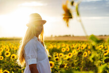 Young Attractive Blonde Woman Posing In Her Designer Dress In A Field Of Sunflowers And Wearing A Hat