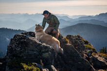 Male Hiker And Dog On Summit O...