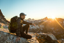 Backpacker Sits On Mountain Summit Enjoying View Of Sunset.