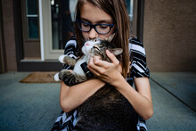 A Pre Teen Girl Kissing Her Cat On The Front Porch