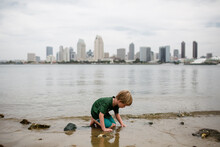 Six Year Old Boy Kneeling In Bay San Diego Skyline In Background