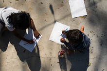 Children Drawing On Paper Outside From Above