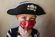 Portrait Of School Age Young Boy Dressed As Pirate With Face Mask On