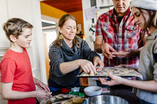 Family Of Four Baking Together During Christmas Eve In Kitchen