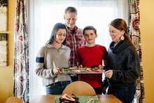 Family Standing By Window With Cookies Decorated Tray