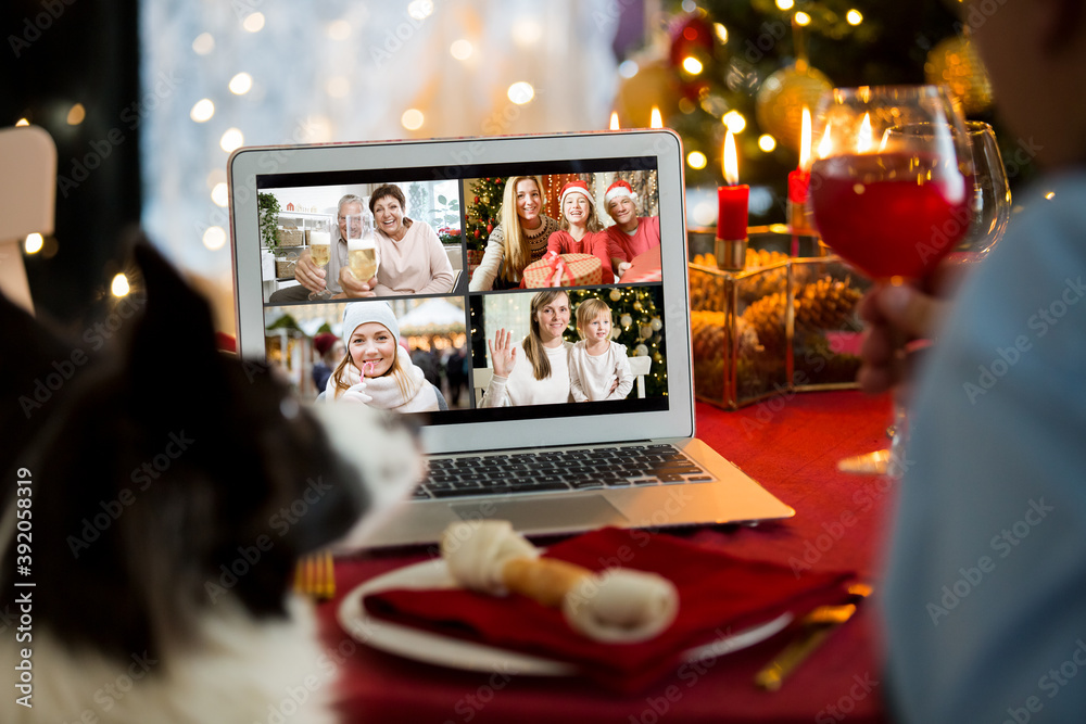 Fototapeta Mature man celebrating Christmas with his dog sitting at served holiday  table with laptop. People greeting their friends on video call using webcam. Christmas eve online. New normal social distancing