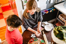 Mother Modeling Holiday Cookies With Son At Kitchen