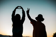 Love And Peace Sign Silhouettes With Colorful Sky - Young People